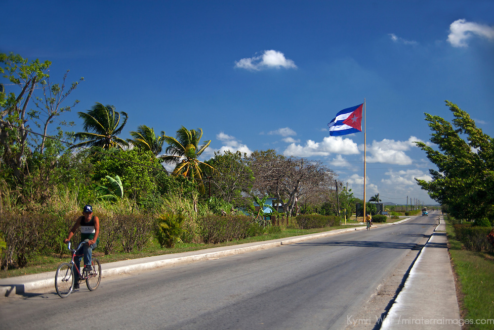 Central America, Cuba, Cienfuegos. Cuban on bike and Cuban flag on road between Cienfuegos and Trinidad.