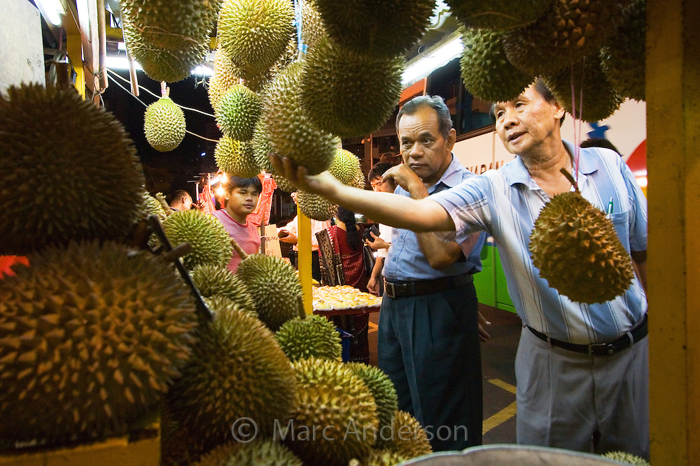 A Man Selling Durians at a Fruit Stall in Kuala Lumpur, Malaysia.