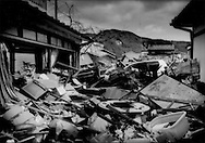 Debris, carried by an earthquake-triggered tsunami 25 m (82 ft.) high pierced into the interior of a house.  Everything beyond the house was flattened and carried away by tons of lumber, automobiles and all manner of personal possessions.  The body of another victim would be pulled from the flotsam only a few minutes later.  There are believed to be 26,000 people either missing or dead and the confirmed death toll from the tsunami has risen above 10,000 souls.