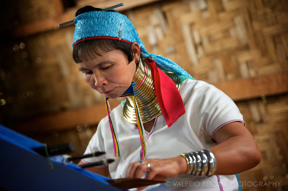 A Padaung woman in traditional dress working at the loom. Famous as Giraffe women, Padaung is a small minority which nowadays preserves the old, unhealty habit to put brass coil elongating their neck mainly to pose for tourists' photos in change of money.