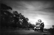 Burmense men riding atop truck on the Mandalay - Pagan.road, Burma 1996.