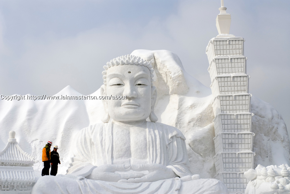 Large snow sculpture of Buddha and Taipei 101 skyscraper at annual Ice and Snow festival in Sapporo Japan
