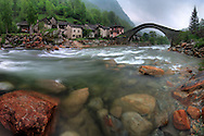 The medieval stone bridge and houses of the small village of Fondo in Valchiusella, Western Alps, Piedmont, Italy. And the Chiusella river roaring in full spate, after seven days of pouring rains. Taken at the end of May, this is a stitch of five vertical frames.