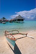 Outrigger canoe on beach and bungalows built over lagoon at Intercontinental Le Moana Bora Bora resort, Tahiti..