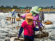 22 FEBRUARY 2017 - BAN LAEM, PETCHABURI, THAILAND: Workers carry salt out of a field during the salt harvest in Petchaburi province of Thailand, about two hours south of Bangkok on the Gulf of Siam. Salt is collected in coastal flats that are flooded with sea water. The water evaporates and leaves the salt in large pans. Coastal provinces south of Bangkok used to be dotted with salt farms, but industrial development has pushed the salt farms down to remote parts of Petchaburi province. The harvest normally starts in early February and lasts until early May, but this year's harvest was delayed by a couple of weeks because of unseasonable rain in January that flooded many of the salt collection ponds.    PHOTO BY JACK KURTZ