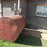 May 2010, Lesotho. Farming activity as the maize harvest is brought in before the winter. An improvised tank is used for the colection of rainwater from the roof.