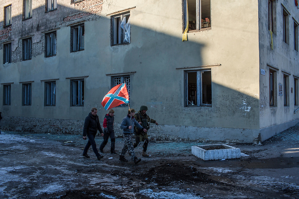 Pro-Russian rebels carry the flag of their self-proclaimed republic of Novorossiya past a damaged building on the central square on February 20, 2015 in Debaltseve, Ukraine. Ukrainian forces withdrew from the strategic and hard-fought town after being effectively surrounded by pro-Russian rebels, though fighting has caused widespread destruction.