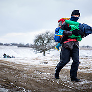 A refugee carries a child across the Macedonian-Serbian border on their way to Western Europe. Near Miratovac, Serbia, January 2016.