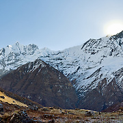 Trekkers explore Annapurna Sanctuary. The sun rises over Machhapuchhre (or Machhapuchhare), the Fish Tail Mountain (on the right; 22,943 feet / 6997 meters elevation) a sacred peak, illegal to climb, in the Annapurna Range of Nepal, Asia. Center left is the sharp peak of Gandharba Chuli (20,500 feet / 6248 meters). Panorama stitched from 3 overlapping photos.