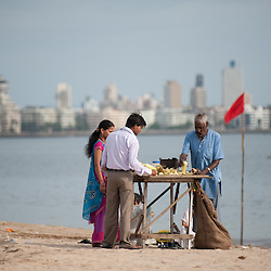An Indian couple buying 'Butta' or  sweet corn on the cob, on an afternoon on chowpati beach. Mumbai, August 2009