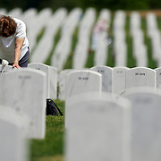 "Frances Gee of Applewood, Co. spends some quiet time at the grave of her husband, Wayne Gee, Friday May 26, 2006 at Fort Logan National Cemetary. She said he was a pilot in the 379th Bomber Group and flew a B-17 out of a base in England during World War II. He passed away last year and she said she was relaying the news of a new great granddaughter in the family and added, ""I was getting a bit emotional, he would have loved her"". Schoolchildren from Traylor Elementary as well as individual families were out at Fort Logan National Cemetary Friday May 26, 2006 to place American flags in front of the more than 70,000 headstones in the cemetary in observance of Memorial Day on Monday. The schoolchildren from Traylor have been coming for 30 years to place flags on the gravesites and the children out there this year were all volunteers as school has already ended for the year at Traylor..(MARC PISCOTTY/ © 2006)"