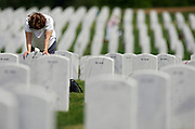 """Frances Gee of Applewood, Co. spends some quiet time at the grave of her husband, Wayne Gee, Friday May 26, 2006 at Fort Logan National Cemetary. She said he was a pilot in the 379th Bomber Group and flew a B-17 out of a base in England during World War II. He passed away last year and she said she was relaying the news of a new great granddaughter in the family and added, """"I was getting a bit emotional, he would have loved her"""". Schoolchildren from Traylor Elementary as well as individual families were out at Fort Logan National Cemetary Friday May 26, 2006 to place American flags in front of the more than 70,000 headstones in the cemetary in observance of Memorial Day on Monday. The schoolchildren from Traylor have been coming for 30 years to place flags on the gravesites and the children out there this year were all volunteers as school has already ended for the year at Traylor..(MARC PISCOTTY/ © 2006)"""