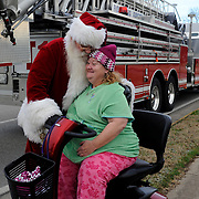 Skip Miller (left), of Smiths Grove, dressed as Santa Claus, hugs Linda Simouth early Sunday morning on Gordon Ave. Bowling Green firefighters and members of the Marine Corps League spent Christmas morning delivering toys to 150 children in the Housing Authority of Bowling Green collected for the local Toys for Tots drive.