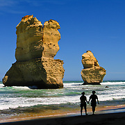 """A romantic couple walks by sea stacks """"Gog and MaGog"""" at the beautiful wild beach at Gibson Steps in Port Campbell National Park, Victoria, Australia. Twelve Apostles Marine National Park protects a collection of miocene limestone rock stacks in the Indian Ocean (or Southern Ocean according to Australian geographers), offshore of the Great Ocean Road. The Great Ocean Road (B100) is a 243-km road along the southeast coast of Australia between Torquay and Warrnambool, in the state of Victoria. Dedicated to casualties of World War I, the Great Ocean Road was built by returned soldiers between 1919 and 1932 and is the world's largest war memorial. Published in """"Light Travel: Photography on the Go"""" book by Tom Dempsey 2009, 2010."""