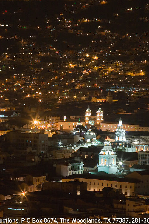 Quito at night with the colonial city in the foreground.  Ecuador.