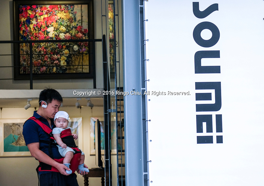 A man carries a baby visits a gallery at the M50 Art Colony in Shanghai, China. Shanghai is the most populous city in China and the most populous city proper in the world. It is one of the four direct-controlled municipalities of China, with a population of more than 24 million as of 2014. It is a global financial centre, and a transport hub with the world's busiest container port. Located in the Yangtze River Delta in East China, Shanghai sits on the south edge of the mouth of the Yangtze in the middle portion of the Chinese coast. The municipality borders the provinces of Jiangsu and Zhejiang to the north, south and west, and is bounded to the east by the East China Sea. A major administrative, shipping, and trading town, Shanghai grew in importance in the 19th century due to trade and recognition of its favourable port location and economic potential. The city was one of five forced open to foreign trade following the British victory over China in the First Opium War while the subsequent 1842 Treaty of Nanking and 1844 Treaty of Whampoa allowed the establishment of the Shanghai International Settlement and the French Concession. The city then flourished as a center of commerce between China and other parts of the world (predominantly Western countries), and became the primary financial hub of the Asia-Pacific region in the 1930s. However, with the Communist Party takeover of the mainland in 1949, trade was limited to socialist countries, and the city's global influence declined. In the 1990s, the economic reforms introduced by Deng Xiaoping resulted in an intense re-development of the city, aiding the return of finance and foreign investment to the city. Shanghai has been described as the &quot;showpiece&quot; of the booming economy of mainland China; renowned for its Lujiazui skyline, museums and historic buildings, such as those along The Bund, the City God Temple and the Yu Garden.(Photo by Ringo Chiu/PHOTOFORMULA.com)<br /> <br /> Usage Notes: This content is