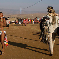 A man in traditioianl animal skins passes young virgin girls at the Zulu royal palace in Nongoma, KwaZulu Natal, South Africa Sept 8, 2007. Thousands of virgin girls attend the annual Reed Dance at the Enyokeni palace from which the Zulu King Zwelethini may choose a bride. Photo Greg Marinovich / Bloomberg News
