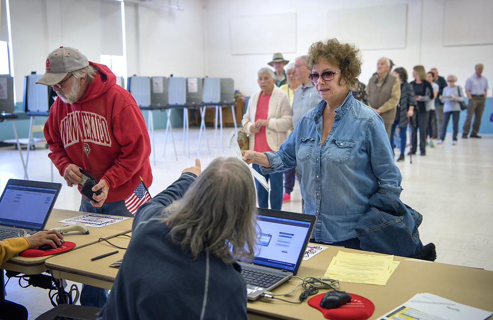 em050217b/a/Don Coviello, left, and Christina Miller get their ballot to vote in the sugar tax election at St. John's United Methodist Church in Santa Fe, Tuesday May 2, 2017. The line of people waiting to vote went around the room and out the door. (Eddie Moore/Albuquerque Journal