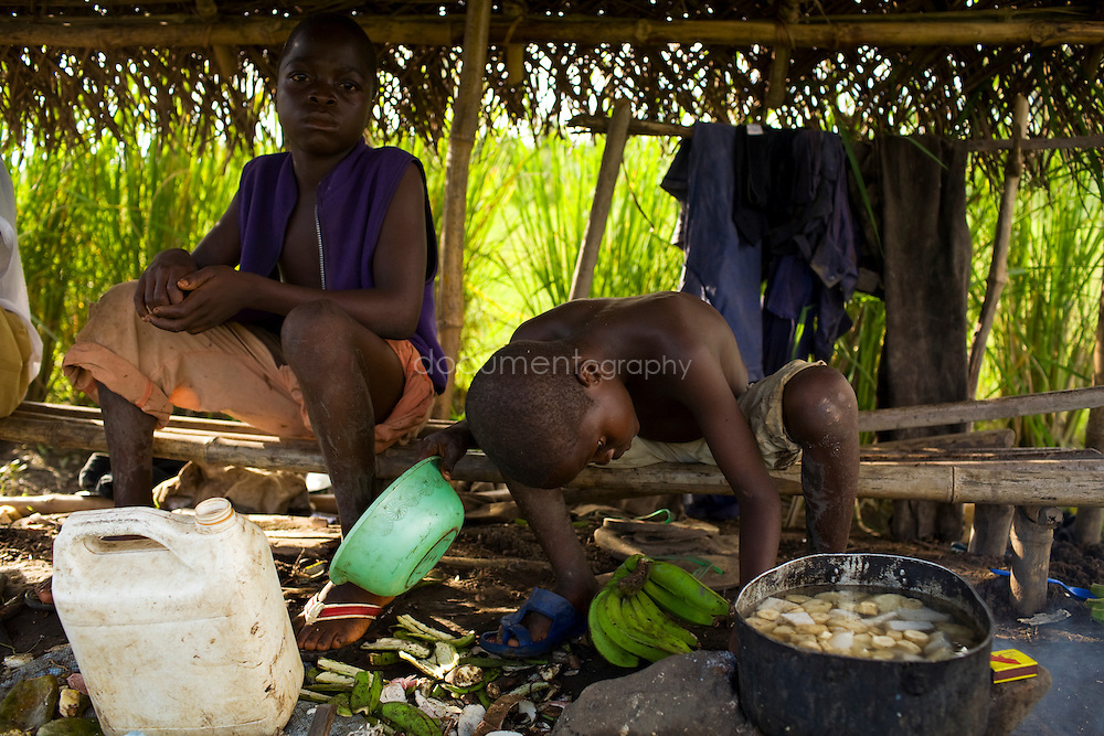 Child cooking while looking after the rice fields, Kingsville #7, Liberia.