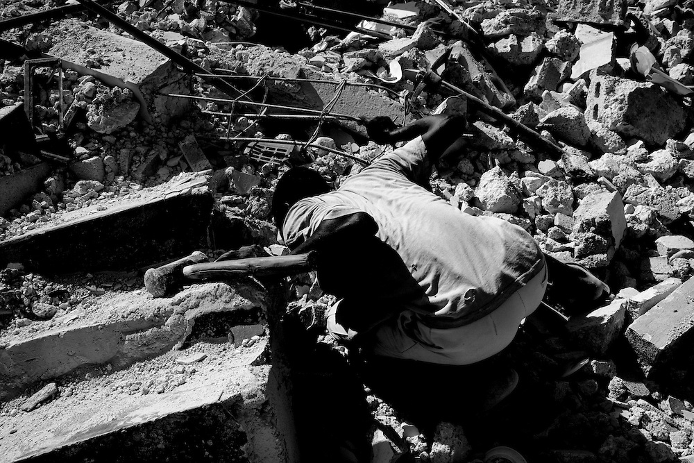 A man looks in the rubble of a collapsed building that was destroyed in the recent earthquake in Port-au-Prince, Haiti.