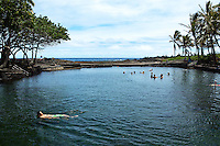 Ahanalui Warm Springs is a spring fed pool - part natural and part manmade. It is also volcanically heated to a balmy 90 degrees! The bottom of the pool is sand and mud and has a slight sulfur smell. The water is brackish but very clear and fish often swim along with the visitors. A small inlet separates the pool from the ocean and allows the fish access to the pool. The area is surrounded by palm trees, green grass and the Pacific Ocean making it a very beautiful and uncrowded tropical retreat.
