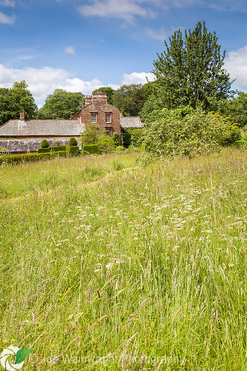 View across a grassy meadow towards the house at Acorn Bank, Cumbria - photographed in June