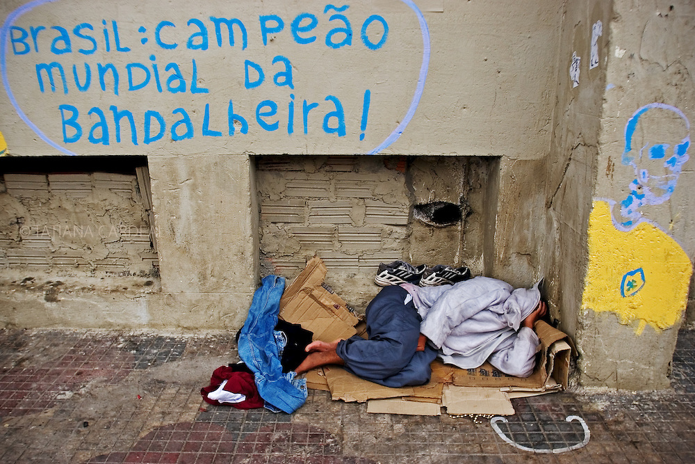"A homeless was sleeping at street, just in front of the Prestes Maia occupation, bellow a graffiti with ironic words: ""Brazil, world's champion of the mess!"" (October, 2006)"