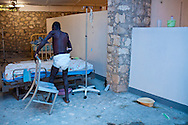 A cholera patient is moved to a new bed at the Hospital Albert Schweitzer on Saturday, October 30, 2010 in Deschapelles, Haiti.