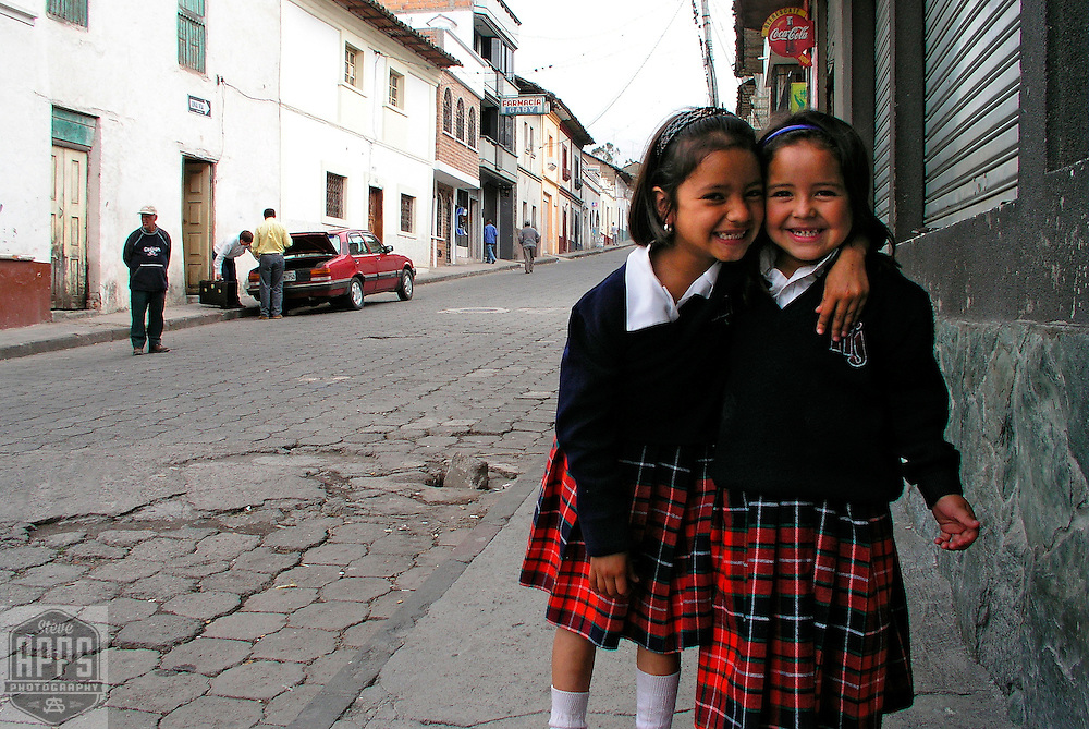 Two girls dressed in the school uniforms pose for a picture outside their mothers business in San Antonio de Ibarra.