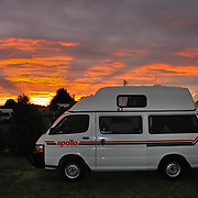 Orange rays of sunset brighten clouds over Peterborough, Victoria, Australia. Apollo campervan.