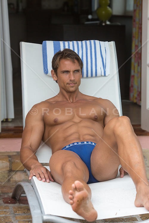 sexy man in briefs sitting on a lounge car while on vacation