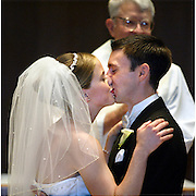 A newly married couple seal the moment with a kiss amongst family and friends.