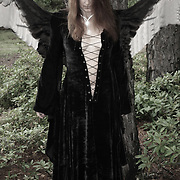 Winged Raven haired Woman in an open front Witch's dress looking downward.