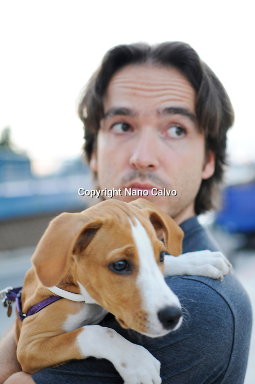 MR Young attractive spanish man holding his puppy