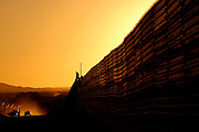 The US/Mexico border fence at sunset on Friday, April 1, 2005 in Aqua Prieto, Mexico.<br />