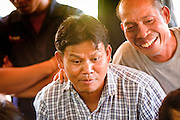 11 APRIL 2010 - PLA PAK, NAKHON PHANOM, THAILAND: Bookies watch the action at a cockfight in Nakhon Phanom province, Thailand. Cockfighting is enormously popular in rural Thailand. A big fight can bring the ring operator as much as 200,000 Thai Baht (about $6,000 US), a large sum of money in rural Thailand. Fighting cocks live for about 10 years and only fight for 2nd and 3rd years of their lives. Most have only four fights per year. Fighting cocks in Thailand do not wear the spurs or razor blades that they do in some countries and most times the winner is based on which rooster stops fighting or tires first rather than which is the most severely injured. Although gambling is illegal in Thailand, many times fight promoters are able to get an exemption to the gambling laws and a lot of money is wagered on the fights. Many small rural communities have at least one cockfighting arena.   PHOTO BY JACK KURTZ