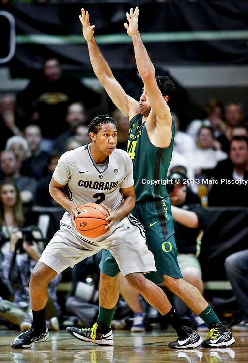 SHOT 3/7/13 8:37:49 PM - Colorado's Xavier Johnson #2 posts up against Oregon's Arsalan Kazemi #14 during their Pac-12 Conference regular season basketball game at the Coors Events Center on the University of Colorado campus in Boulder, Co. Colorado won the game 76-53..(Photo by Marc Piscotty / © 2013)