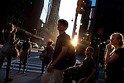 People wait to cross the street on Broadway as the sun sets on Columbus Circle, New York on June 23, 2012.