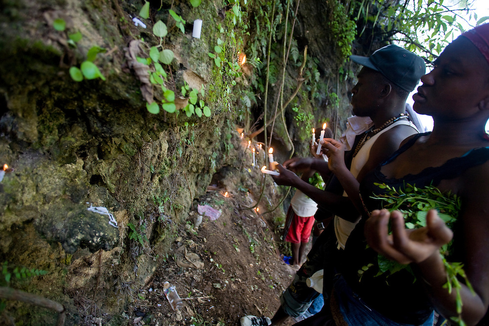 Supplicants light candles to invoke the support of the loa, or spirits.                          Haitian pilgrims are gathered at the waterfall at Saut d'Eau on July 16th, the anniversary of the 1983 sighting of the Virgin Mary, alternately identified as the Vodou loa of Erzulie Freda, the Goddess of Love..The waterfall at Saut D'Eau is the site of the largest Vodou and Catholic pilgrimage in Haiti. A second sighting of the Virgin was reported during the American occupation. Each year, thousands of Haitian pilgrims make their way to Saut D'Eau to bathe in the sacred water and revel in the presence of the loa, particularly Erzulie and Damballah the Serpent, father of all life and keeper of spiritual wisdom, who is said to live in the falls. The water is believed to be curative and many women come to Saut d'Eau seeking fertility.
