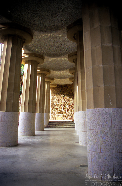 Gaudi's wavy bench in Parc Guell is supported by tall pillars. Antoni Gaudi's Park Guell is a UNESCO World Heritage Site.