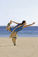 MR Yoga teacher and artist Lena Tancredi, doing yoga on a peaceful beach of Ibiza, Spain