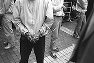 Men hold a rope to form a barrier, in Tokyo, Japan.