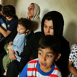 "A family from Fallujah rests inside a home, Baghdad, Iraq, April 12, 2005. They escaped by crawling on their knees to an ambulance and then traveling to Baghdad in a refrigerated meat truck. Intesar Jamil, in black, said, ""Every time we tried to leave the house to get food, the Americans would shoot at us.""  Hospital officials in Fallujah report more than 600 killed and more than 1200 wounded, most of which they say were women, children and elderly."