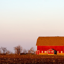 The last light of the day glows off of the red sides of a large barn in rural Illinois.