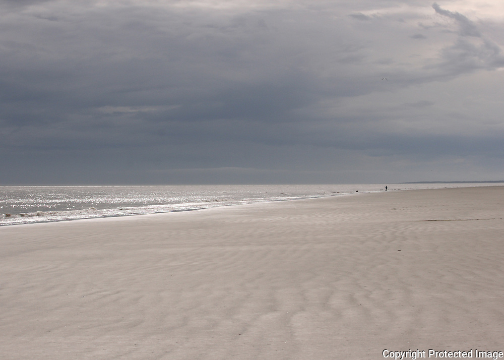 A lone beachcomber walks on a Jekyll Island beach in front of an approaching storm.