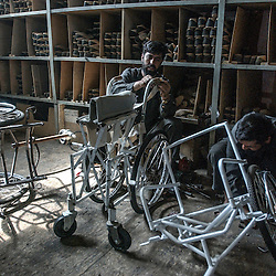 Afghans make wheel chairs and plastic limbs for patients at the orthopedic center set up by the International Committee for the Red Cross in Kabul, Afghanistan August 5, 2002.  (Photo  by Ami Vitale)