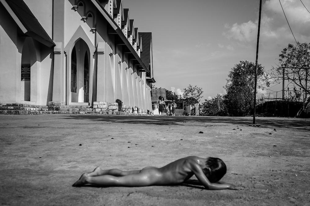 A boy dries himself in the sun after a swim near Sapa, northern Vietnam