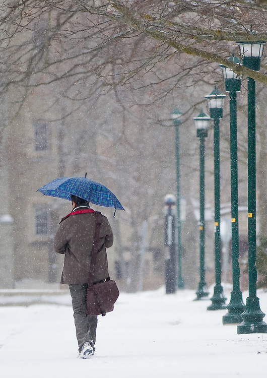 London, Ontario ---12-01-02--- A man walks with an umbrella down a snow covered path at the University of Western Ontario in London, Ontario, January 2, 2012. London was under a snow squall warning for much of Monday wit up to 40cm predicted by the end of storm.<br /> GEOFF ROBINS The Globe and Mail