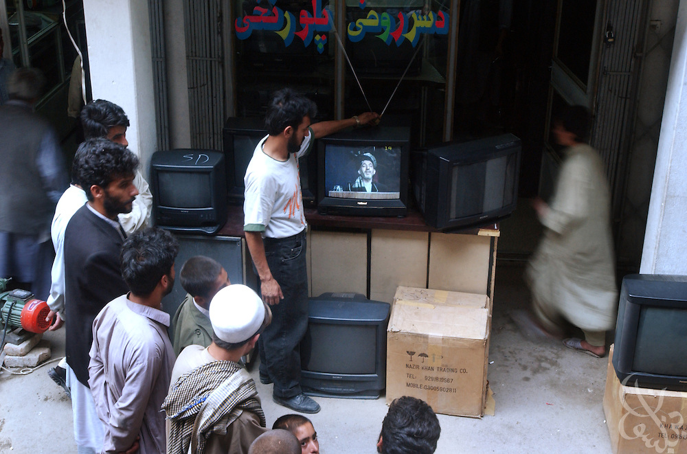 Afghan men watch television coverage of interim leader Hamid Karzai addressing the country's Loya Jirga June 11, 2002 in Kabul, Afghanistan. The Loya Jirga, Afghanistan's grand council of 1,550 delegates, convened June 11, 2002 to choose a transitional government.