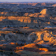 The badlands of Theodore Roosevelt National Park, North Dakota, are turned golden by the setting sun in this view from the Painted Canyon Overlook.
